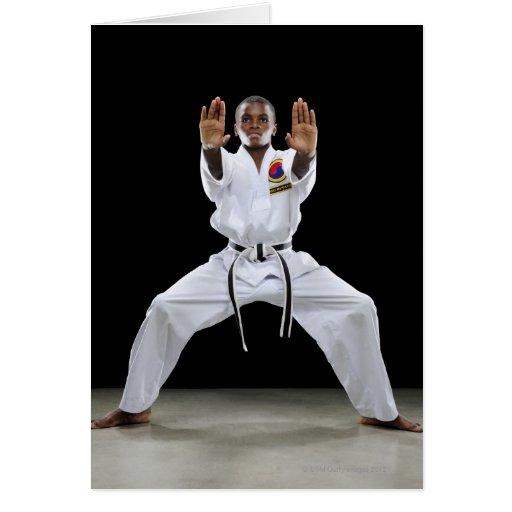 Un muchacho (15 años) en un uniforme del karate co felicitaciones