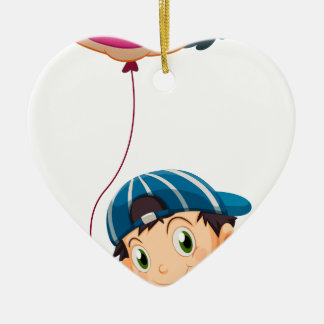 Un muchacho que sostiene un globo del payaso ornamento para arbol de navidad