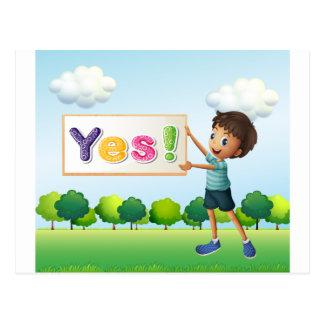 Un muchacho que sostiene un letrero postal