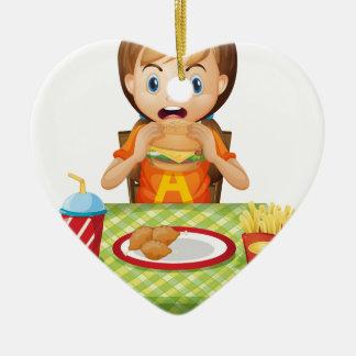 Un niño que come en un restaurante de comida adorno de cerámica en forma de corazón