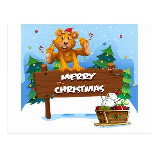 Un oso juguetón que juega cerca del navidad postal