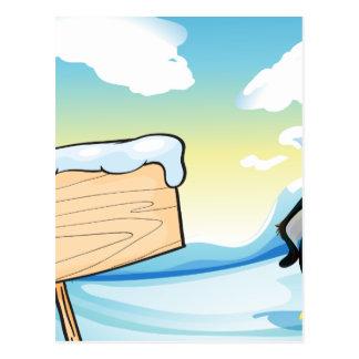 Un pingüino al lado del letrero de madera vacío postal
