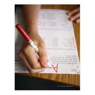 Un profesor de escuela secundaria pone un grado en postal