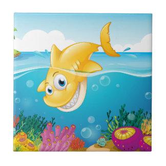 Un salto amarillo del tiburón en el mar azulejo