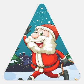 Un Santa sonriente que tira del trineo de madera Pegatina Triangular