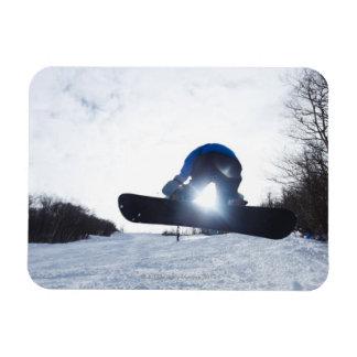 Un snowboarder de sexo femenino toma el aire en imán
