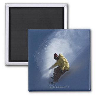 Un snowboarder de sexo masculino coge la luz imán