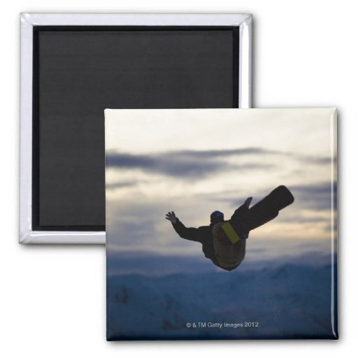 Un snowboarder de sexo masculino hace un salto mor imán de frigorifico