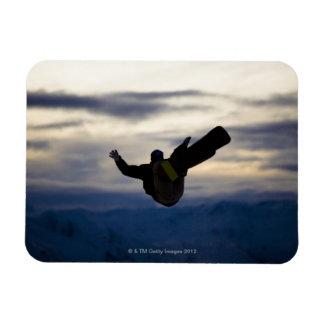 Un snowboarder de sexo masculino hace un salto mor imanes
