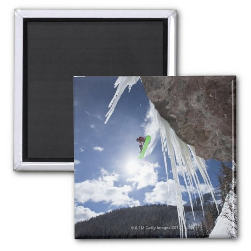 Un snowboarder de sexo masculino salta de una casc imán para frigorífico