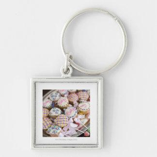 Una bandeja de magdalenas del traqueteo del bebé e llaveros