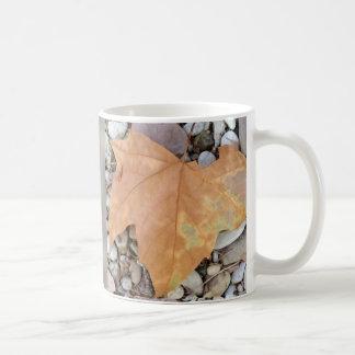 una hoja oxidada en los guijarros taza de café