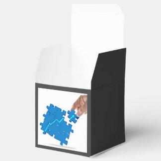 Una imagen de una mano que termina un rompecabezas caja para regalo de boda