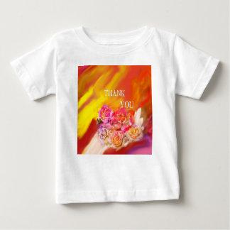 Una mano de gracias tiende por completo hacia camiseta de bebé