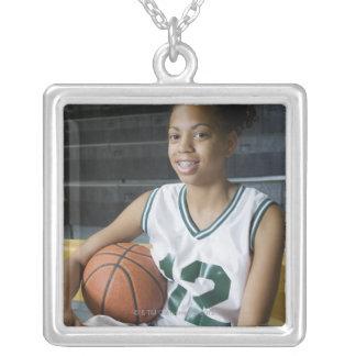 Uniforme del baloncesto del adolescente que lleva  pendientes