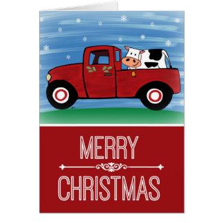 Vaca de las Felices Navidad en una tarjeta roja