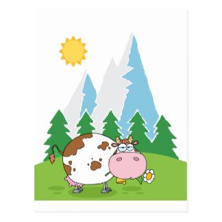 Vaca lechera de la montaña con la flor en boca postal