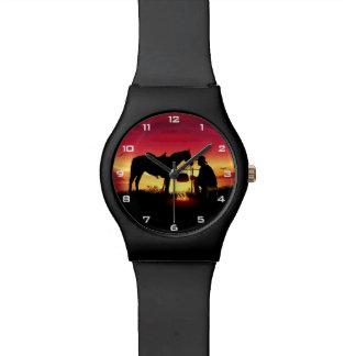 Vaquero y caballo en el reloj de la puesta del sol
