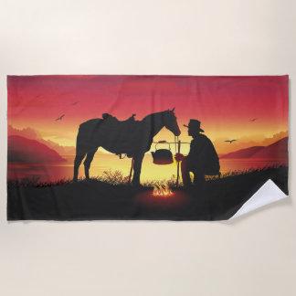 Vaquero y caballo en la toalla de playa de la