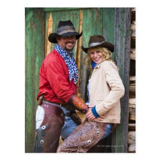 Vaquero y vaquera que llevan a cabo las manos postal