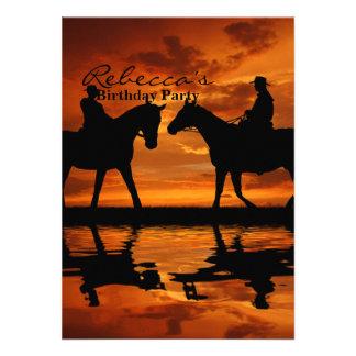 Vaqueros del montar a caballo en puesta del sol