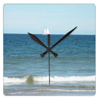 Velero en el océano del reloj de la playa de Cape