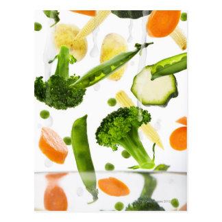 Verduras frescas con agua que cae en un cuenco postal
