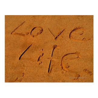Vida del amor escrita en arena postales