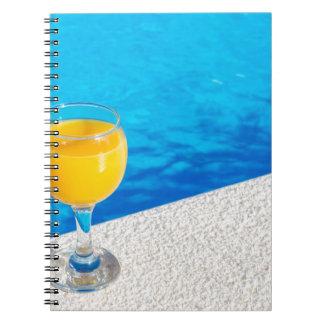 Vidrio con el zumo de naranja en el borde de la cuaderno