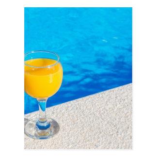 Vidrio con el zumo de naranja en el borde de la postal