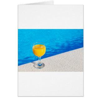 Vidrio con el zumo de naranja en el borde de la tarjeta