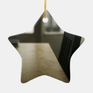 Wooden table desk and chair in empty room with win adorno navideño de cerámica en forma de estrella