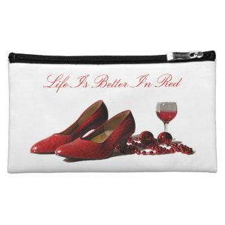Zapatos rojos del tacón alto y vino rojo